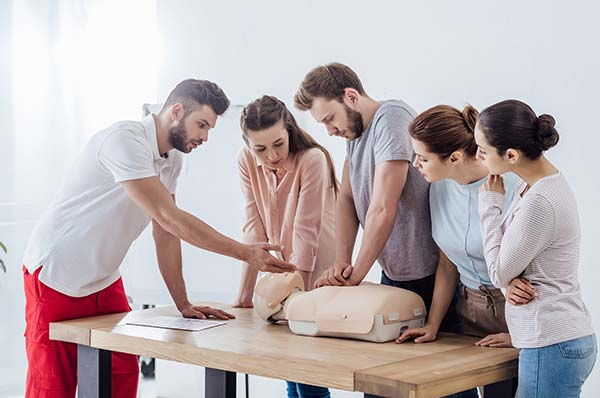 instructor giving directions to four people on CPR