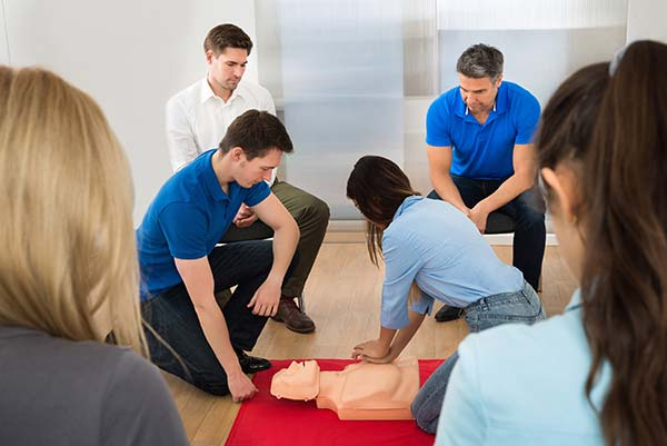 woman performing CPR on a dummy