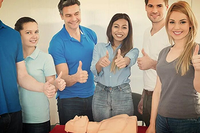 group of smiling people standing around a dummy